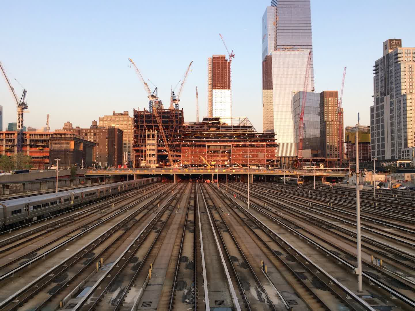 A picture of many parallel subway tracks, with cranes building skyscrapers in the background.