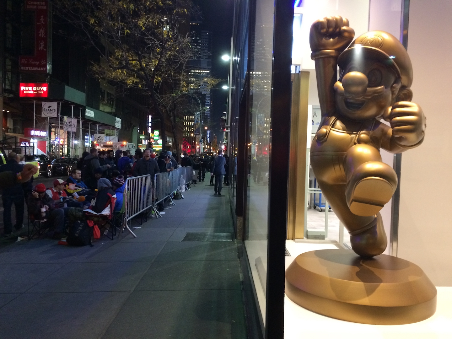 A lineup in front of the Nintendo NYC Store, with a golden-coloured Mario statue in the shop's window.